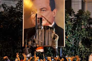 Demonstrators in Cairo tear down a poster of former-President Hosni Mubarak.