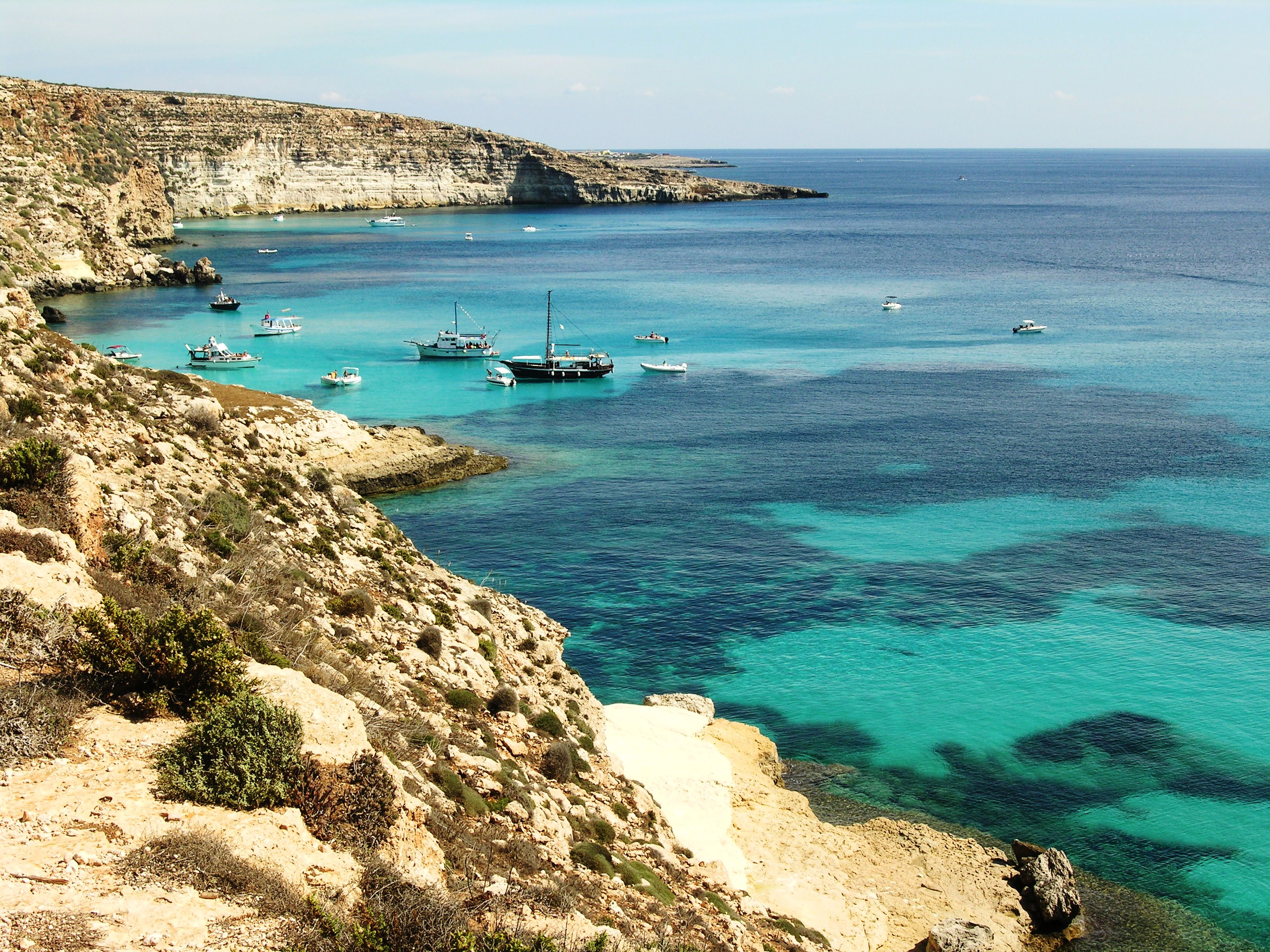 Boats off the shore of Lampedusa, photo courtesy of Wikimedia Commons