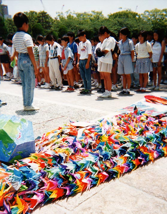 Children sharing a moment of silence before a memorial in the Hiroshima Peace Park. Photo credit: Andrew Dunn, 1990, courtesy of Wikimedia Commons.