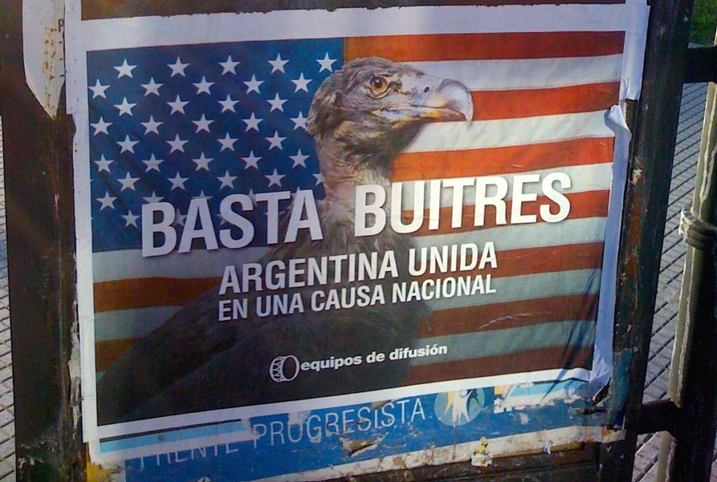 "A political poster from a Buenos Aires street advocating ""Enough Vultures! Argentina united in a national cause."""