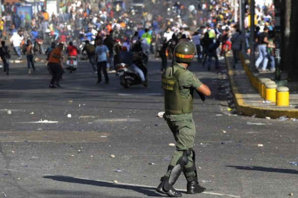 Students clash with National Guards members during an opposition demontration against the government of Venezuelan President Nicolas Maduro, in Caracas on February 12, 2014. Unidentified assailants on a motorcycle fired into a crowd of anti-government protesters, leaving at least two people wounded and a pro-government man dead.  AFP PHOTO / LEO RAMIREZ